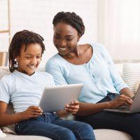 afro-mom-and-daughter-doing-school-homework-on-sof-QHHEQDH.jpg